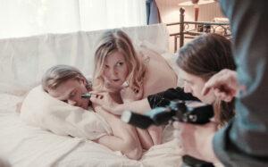 Kuvaaja kuvaa pariskuntaa sängyllä