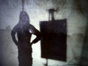Naisen silhuetti valokaluston edessä.