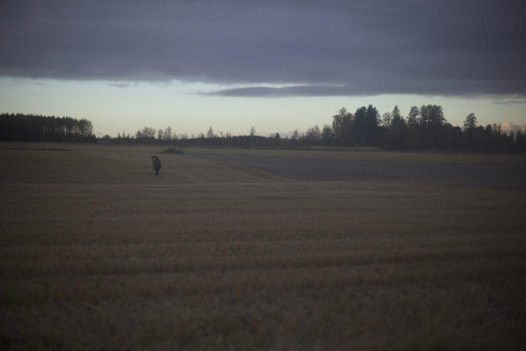 Elokuvatyöntekijä seisoo puomin kanssa keskellä peltoa.