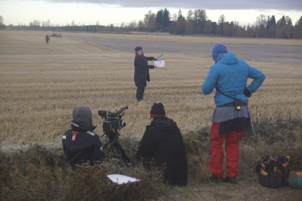 Elokuvatyöntekijöitä kuvauksissa pellolla. Nainen pitelee klaffia. Kuvaukset ovat alkamassa.