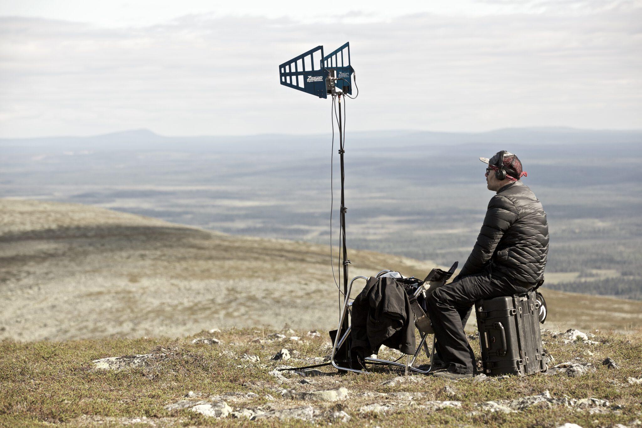 Elokuvatyöntekijä istuu yksin ja tuijottaa aavaa maisemaa.