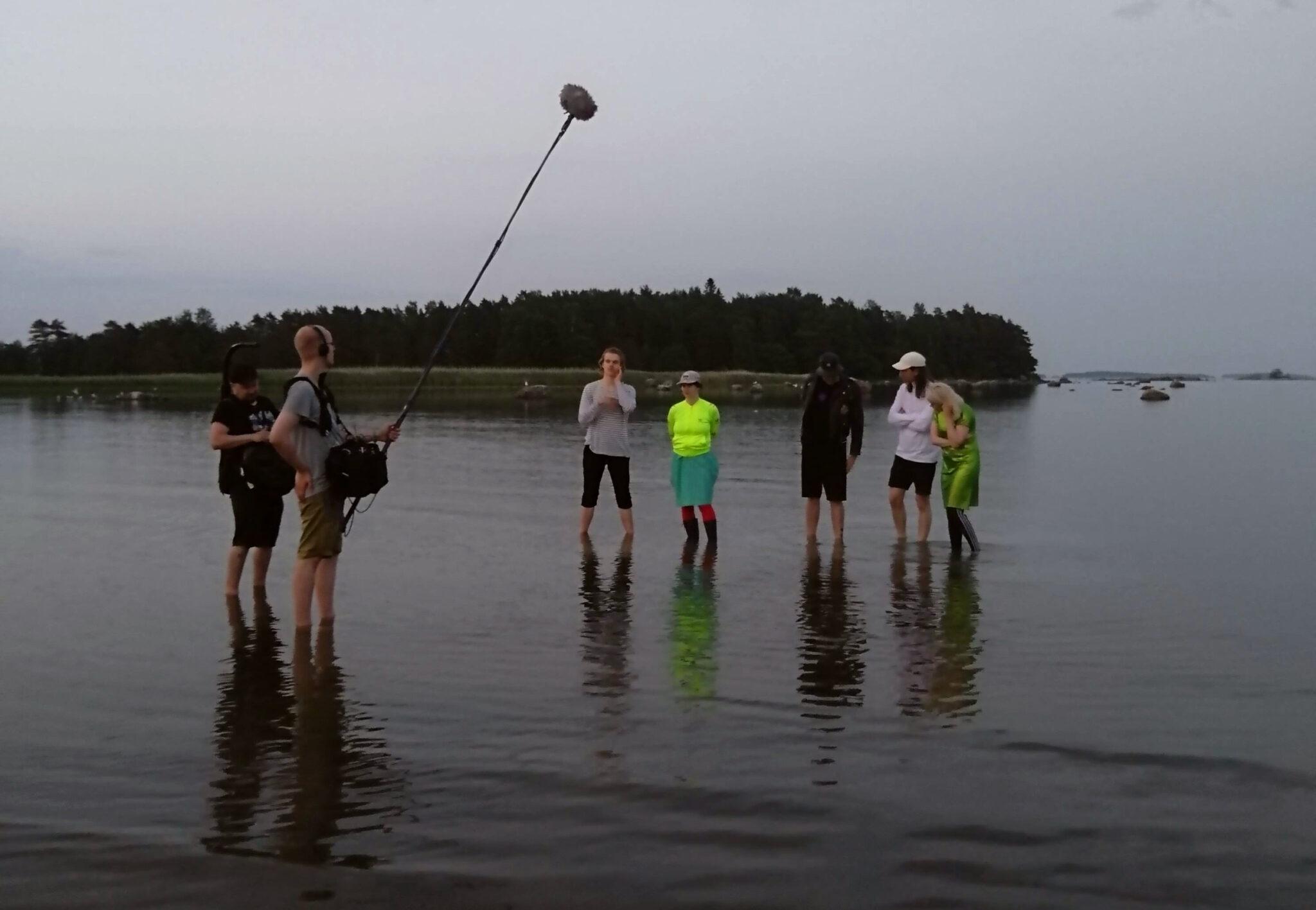 Elokuvan Fucking with Nobody -kuvauksista, jossa tuotantoryhmä ja näyttelijät seisovat keskellä järveä.
