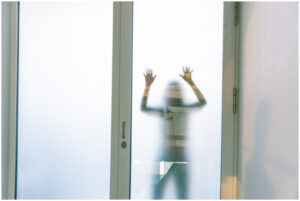Naisen sihuetti sumean lasioven takana.